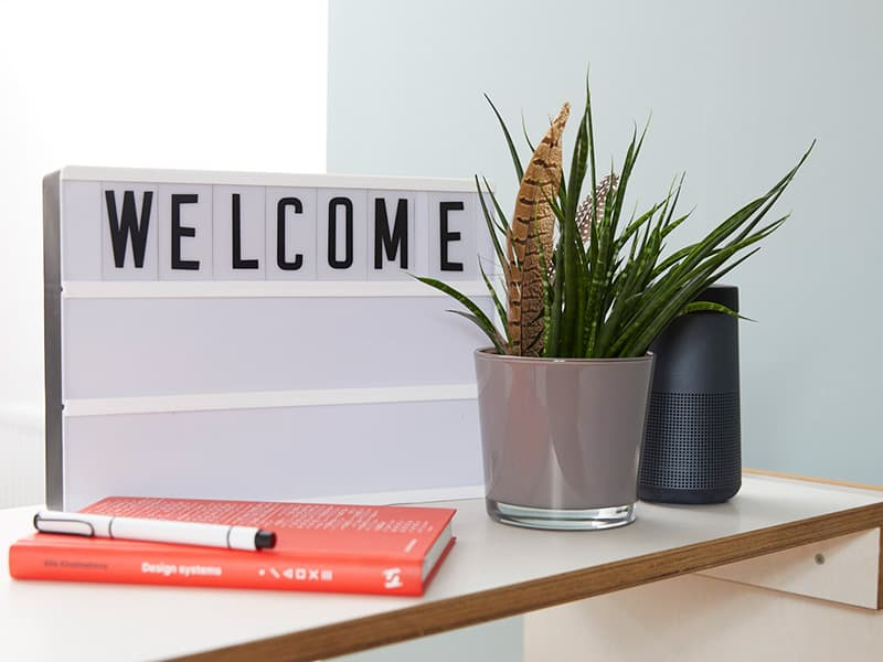 A sign labelled 'welcome' and a few potted plants at the office.